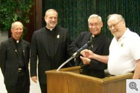 Grand Knight Dick Breckon presents a check to Bishop Taylor with Monsignor Friend and Father Elser observing.